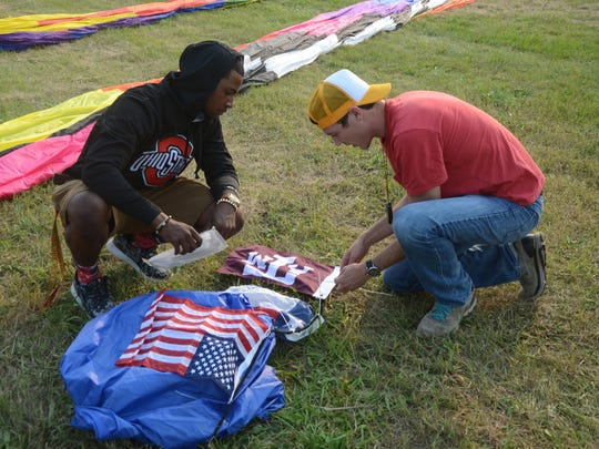 Pilot Christopher Cliver, right, and Darian Brown, of Battle Creek, a member of the the crew install an American, Texas, and Texas A&M flag on the balloon crown line Saturday.