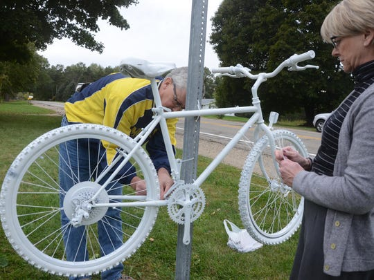 Drew and Diane Peters place a white Ghost Bike at the scene of last week's fatal accident.