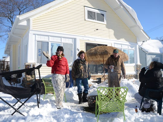 Kathy Kelley, second from left, and neighbors partied on Monday in the face of winter at her home on East Avenue North.