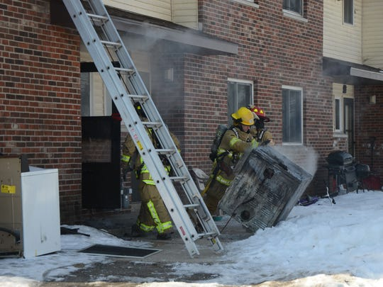 Battle Creek firefighters remove a clothes dryer from inside the apartment.