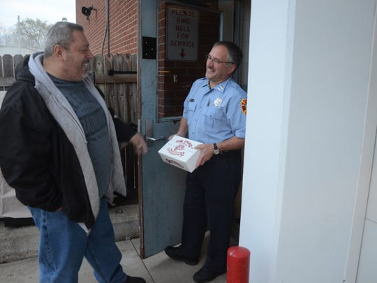 Alphonse Bifulco delivers some doughnuts to Capt. Mark Burkhart at the Battle Creek Fire Department.