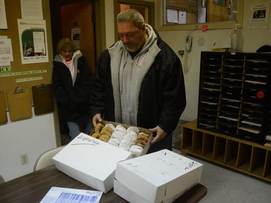 Alphonse Bifulco delivers some doughnuts to the Battle Creek Public Schools bus garage and drivers, including Mindy Drogus.