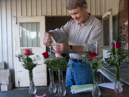 Cliff Shell prepares orders for delivery Wednesday at Ruth Messmer Florist in Fort Myers.