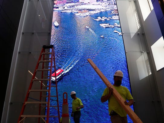 Workers walk past a 60-foot tall and 20-foot wide video