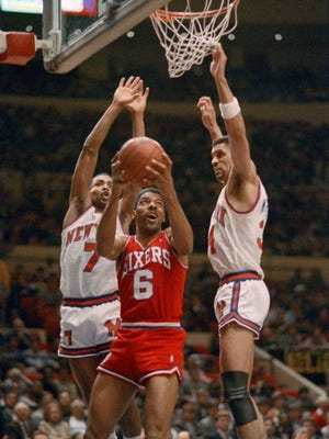 Philadelphia 76ers Julius Erving goes for the basket between New York Knicks' Gerald Henderson, left, and Kenny Walker during NBA action, Apr. 7, 1987 at New York's Madison Square Garden. This was Erving's last game at Madison Square Garden as he is retiring from professional basketball at the end of the season. The Knicks beat the 76ers 108-101.