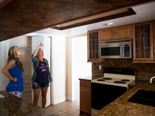 House flipping duo Heather Caine, left, and Katie Werchek inspect a recently purchased house in Golden Gate City on Friday, May 5, 2017. Unlike many brokers that will simply lower the price on a house to get it sold, Caine invests a few thousand dollars to add simple upgrades and decorations.