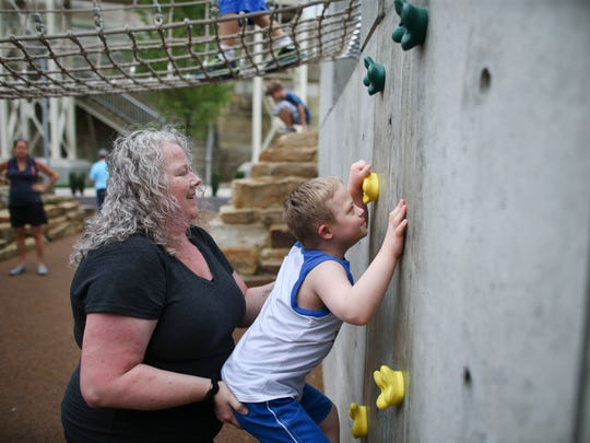 In this Tuesday, July 7, 2015 photo, Steven Heffron, 6, and his mother, Denise Watts, play in Smale Riverfront Park in downtown Cincinnati.