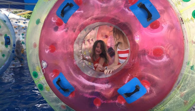 Josie Balkin, left, smiles as she plays with her twin sister, Georgia Balkin, in the inflatable bubble. The 6-year-old twins were excited to spend a day at the fair before school begins.