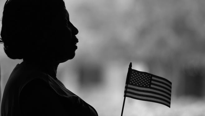 Rosemary Sibanda holds an American flag her daughter, Lyn Mguquka, from Zimbabwe, received when she became a US citizen, during a Naturalization Ceremony at IUPUI, Thursday, April 27, 2017.