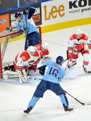 Checkers goaltender C.J. Motte has plenty of company in his net as Admirals center Felix Girard shoots Tuesday in Milwaukee's loss to Charlotte at the UW-Milwaukee Panther Arena.