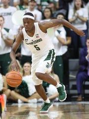Michigan State guard Cassius Winston brings the ball