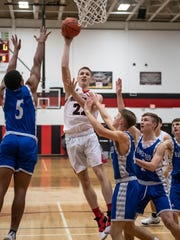 Marshall's Jeremy Luciani (22) goes for the hoop during first half action against Harper Creek Friday evening.