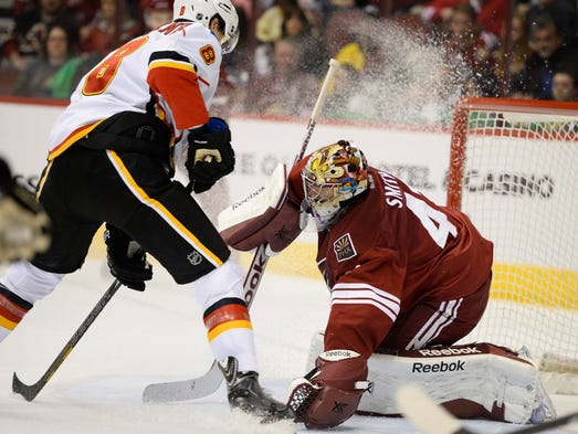 Coyotes goalie Mike Smith (41) makes a save in front of Flames center Joe Colborne (8) during the second period.