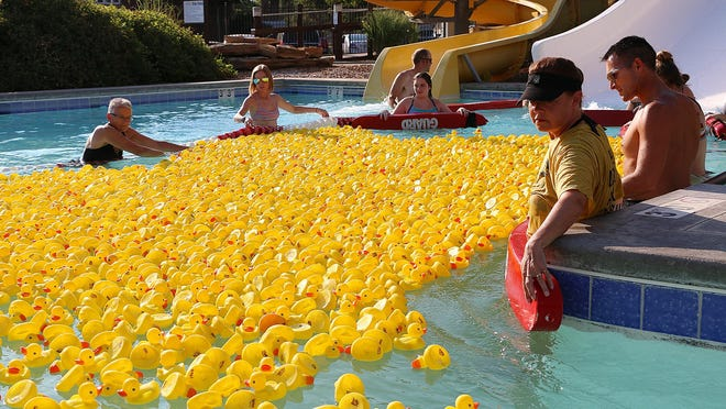 Volunteers help guide the rubber ducks around the lazy river at the Hays Duck Derby on Wednesday at Hays Aquatic Park.