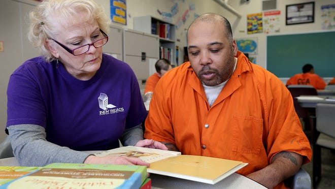 Lucia Sheehan, of Indy Reads, works with inmate Kent Mitchell as he records himself reading a book. Sheehan sent the recorded book to Mitchell's son. Volunteers from Indy Reads teach literacy classes at Marion County Jail II and prepare inmates to find jobs when they are released.