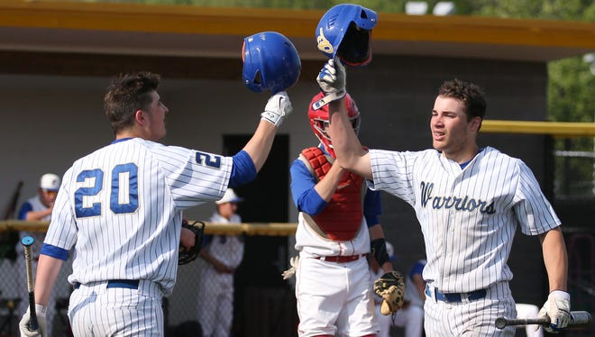 Webster Schroeder's Shane Marshall, right, celebrates with teammate Phil Ferranti, left, after scoring on a double by teammate Sean O'Neill in the third inning of their Section V Class AA baseball tournament semifinal against Fairport  in May.