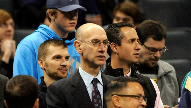 NBA Commissioner Adam Silver (center) watches the game between the Charlotte Hornets and the Phoenix Suns at Time Warner Cable Arena.