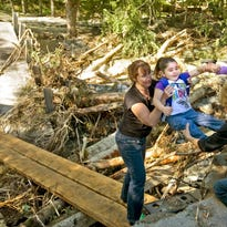 Lisa Hamilton lifts 3-year-old Aubree Chapman out of the wreckage of a bridge on Cooke Road while her mother, far left, waits her turn as they evacuate their home after heavy flooding from Tropical Storm Irene in Brattleboro on Monday, Aug. 29, 2011.