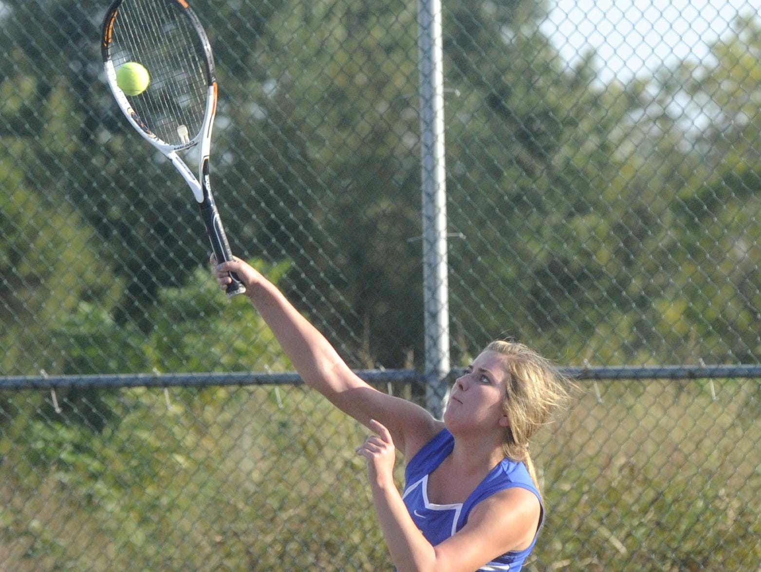 Mountain Home's Taylor Hasselwander hits an overhead shot during her and Elizabeth Lewis' doubles match against Bergman on Tuesday at Mountain Home Athletic Club.