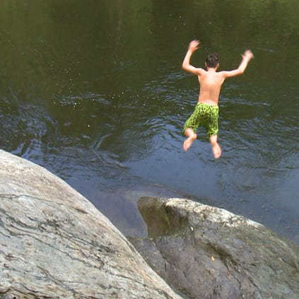 12-year-old Emery Benson, a Boy Scout from Maryville, jumps in for a swim at the Townsend Wye.