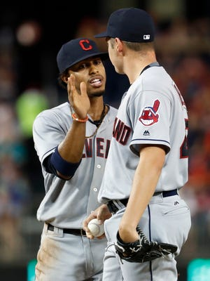 Cleveland Indians shortstop Francisco Lindor, left, reacts with starting pitcher Trevor Bauer as bench coach Brad Mills walks to relieve Bauer during the seventh inning Tuesday. The Indians won 3-1.