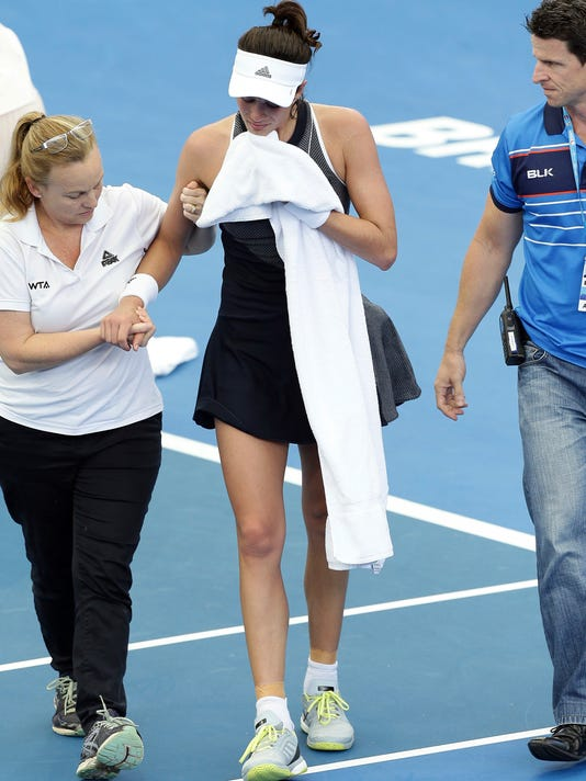 Garbine Muguruza of Spain leaves the court after she suffered cramps in her match against Aleksandra Krunic of Serbia during the Brisbane International tennis tournament in Brisbane, Australia, Tuesday, Jan. 2, 2018. Muguruza fell to the court behind the baseline in the third set before retiring from her opening match. (AP Photo/Tertius Pickard)