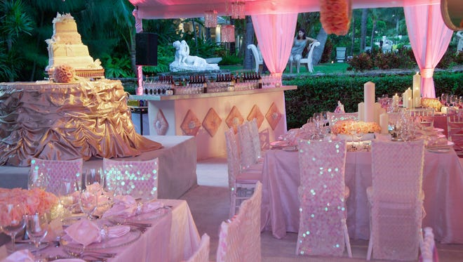 A tent is draped with pink fabric for a wedding reception.