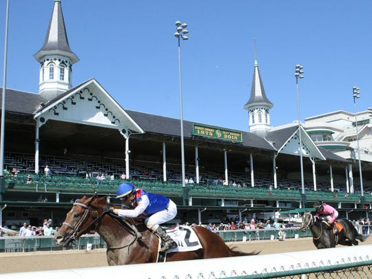 Horses run by the Twin Spires at Churchill Downs.