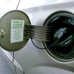 A gas tank cover on a vehicle indicates that E85 fuel or unleaded gasoline can be used. E85 fuel is a blend of 85 percent ethanol and 15 percent gasoline.