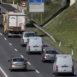 A convoy of police vehicles follow a refrigerated truck being towed along a highway near Neusiedl am See, Austria, on Aug. 27.