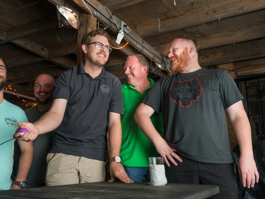 From left, My Bacon Don't Need No Viagra team members Joel McMillan, Bill Sanders and Kyle Phillips have a laugh while competing in the lightning round during trivia night at Goat Lips Chew & Brewhouse in Pensacola on Wednesday, June 13, 2018.
