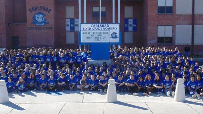The student body at the Carlsbad Sixth Grade Academy posed in front of the school wearing their matching t-shirts.