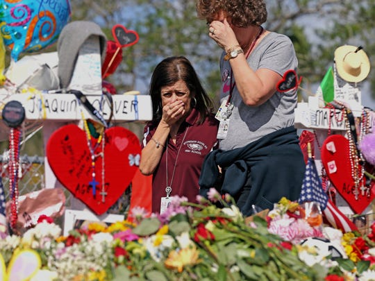 Marjory Stoneman Douglas High School administrative employees Margarita LaSalle, left, and JoEllen Berman, walk along the hill near the school in Florida lined with 17 crosses to honor the students and teachers killed on Valentine's Day. Teachers and staff returned to the school Feb. 23 for an orientation and to get ready to receive students the next week.