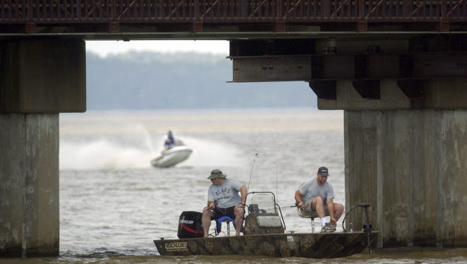 A pair of fishermen try their luck under Pelahatchie Bay causeway as a personal watercraft skips across the waves behind them on the Ross Barnett Reservoir in Rankin County Sunday, taking advantage of a sunny day with temperatures in the low 80Õ.