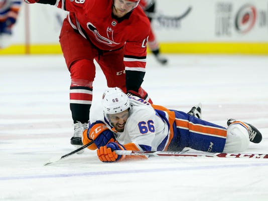 Carolina Hurricanes' Elias Lindholm (28), of Sweden, and New York Islanders' Joshua Ho-Sang (66) chase the puck during the first period of an NHL hockey game in Raleigh, N.C., Sunday, Nov. 19, 2017. (AP Photo/Gerry Broome)