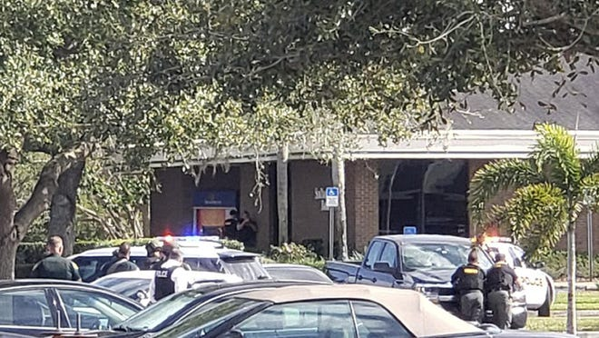 Law enforcement officials take cover outside a SunTrust Bank branch, Wednesday, Jan. 23, 2019, in Sebring, Fla. Authorities say they've arrested a man who fired shots inside the Florida bank.