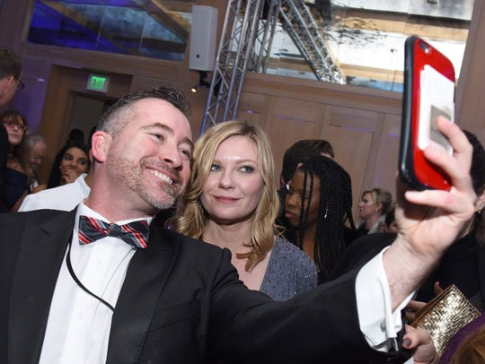 Actress Kirsten Dunst takes a selfie with a guest at