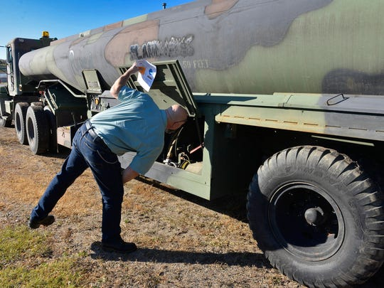 Cold Spring Public Works Director Paul Hoeschen on Wednesday examines a pump in a 5,000 gallon Army surplus tank trailer the city bought recently. The city bought two surplus semi tractors last year. The trailer will be converted to haul biosolids.
