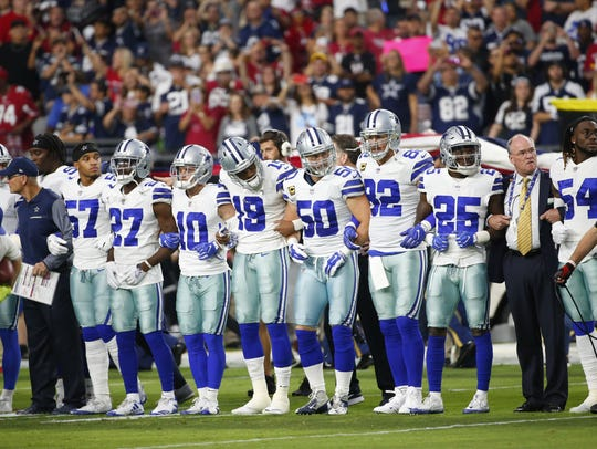 Dallas Cowboys players link arms before the National