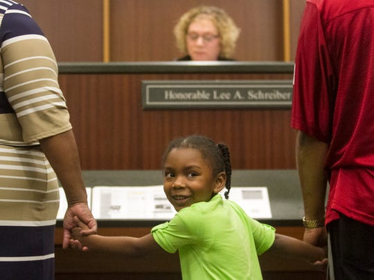 Ja'Riyyah Clark smiles as her adoption is finalized on Saturday, November 21, 2015 in Fort Myers.