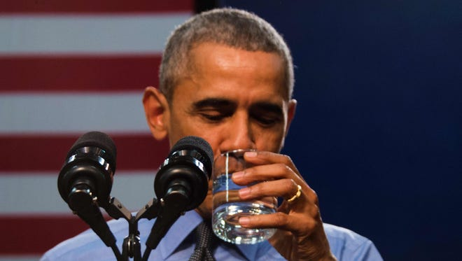 President Obama drinks a glass of water as he speaks at Flint Northwestern High School in Flint, Michigan Wednesday after meeting with locals for a neighborhood roundtable on the drinking water crisis.