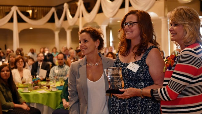 Andrea Saffle, left, and Emily Curry, center, accept the Outstanding Economic Impact award for Southern Prohibition Brewing during the Mississippi Main Street Annual Awards Luncheon on Thursday at the Old Capitol Inn in Jackson.