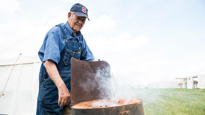 """Daniel Young, 82, of Bassett, Virginia, cranks a fan on a coal forge at the Gettysburg re-enactment site on Thursday, June 29, 2017. Young operates a tent called """"The Blacksmith"""" which sells an assortment of Civil War-period merchandise."""