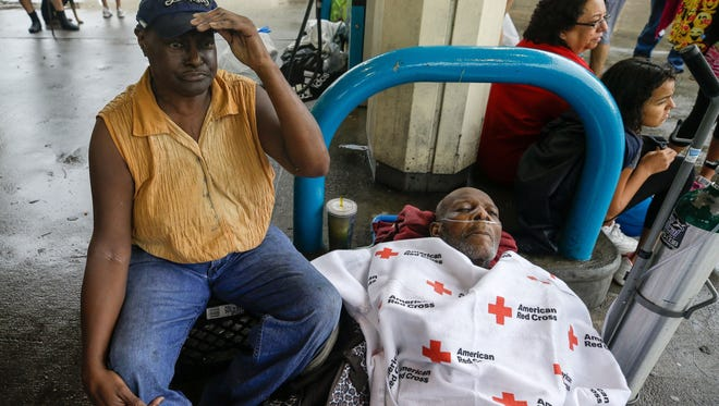 Ruby Young waits with her husband, Claude Young, after being rescued from their flooded home by boat and taken to a pickup point on Sunday, Aug. 27, 2017. Claude Young had many medical issues from a stroke in May.