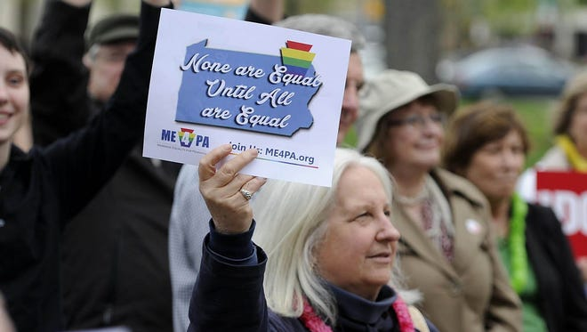 A woman holds a sign in support of marriage equality during in Erie, Pa., on May 20, 2014.