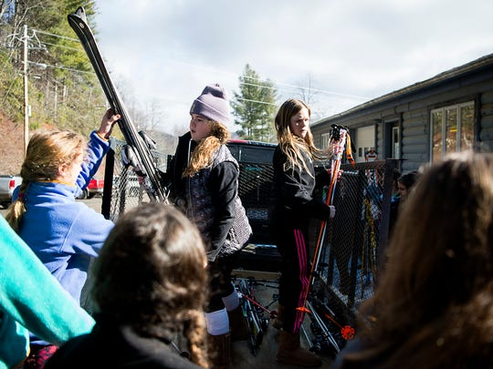 Sixth graders Summer Willard, left, and Anna Clark, right, pass out skis to their fellow classmates Thursday Feb. 9, 2017 at the Cataloochee Ski Area in Maggie Valley. The Girls French Broad River Academy is a school that emphasizes outdoor learning, through field lessons.