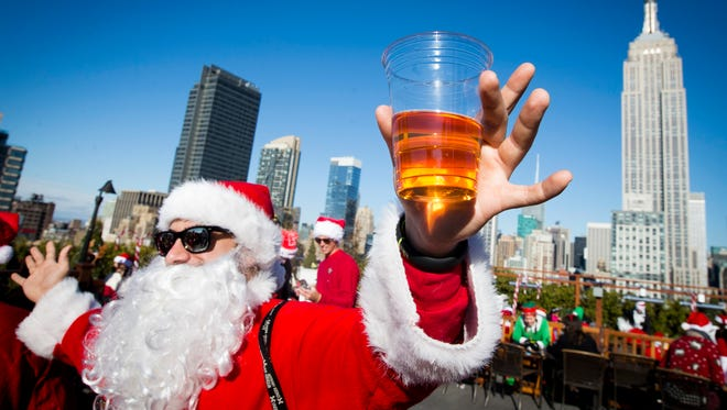 A man dressed as Santa Claus holds a beer as he and others participate in SantaCon on a rooftop bar Saturday, Dec. 13, 2014, in New York.   SantaCon organizers retained lawyer Norman Siegel  last week as part of an effort to tame the excesses of the daylong party.  Siegel said the government cannot ban SantaCon. But he said the government can reasonably regulate the event.