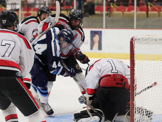 Bay Port Pirates forward Max Moore (44) fights for the puck in front of the net against Sun Prairie Cardinals defenseman Noah Nehmer (20) in a quarterfinal match at the 2017 State Hockey Tournament at Veterans Memorial Coliseum on Thursday, March 2, 2017, in Madison, Wis. Sun Prairie won the match, 3-2. 