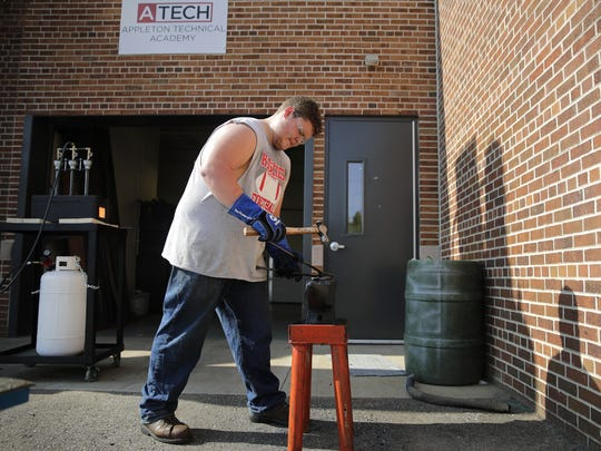 Brandon Kluba, a senior at Appleton Technical Academy, uses a hammer and anvil along with a portable forge to create a set of tongs that will be used for the forge in the future in 2017 in Appleton. The academy is located at Appleton West High School.
