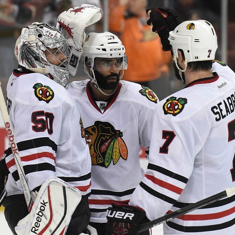 Chicago Blackhawks goalie Corey Crawford (50), defenseman Johnny Oduya (27) and defenseman Brent Seabrook (7) celebrate the 5-2 victory against the Anaheim Ducks in Game 7 of the Western Conference final.